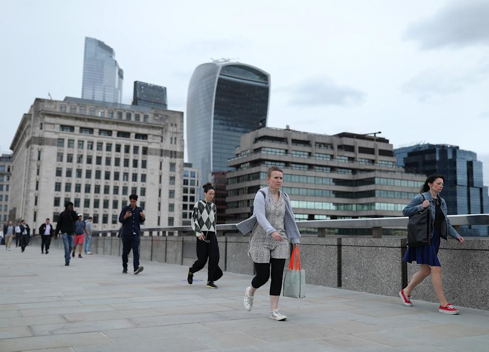 Commuters crossing London Bridge during evening rush hour. Train services have been ramped up from Monday in England and Wales reopen and workers are encouraged to return to offices.