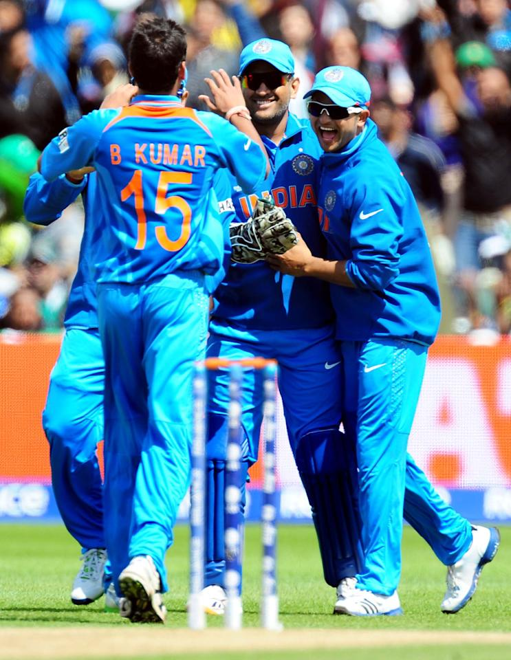 India's players Mahendra Dhoni (centre) and Suresh Raina (right) celebrate Pakistan's Mohammad Hafeez wicket bowled B. Kumarcaught C. Dhoni for 27 during the ICC Champions Trophy match at Edgbaston, Birmingham.
