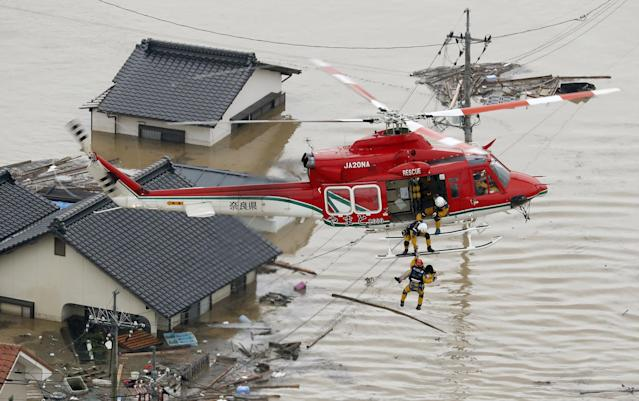<p>An aerial view shows a local resident being rescued from a submerged house by rescue workers using helicopter at a flooded area in Kurashiki, southern Japan, in this photo taken by Kyodo July 7, 2018. (Photo: Kyodo via Reuters) </p>