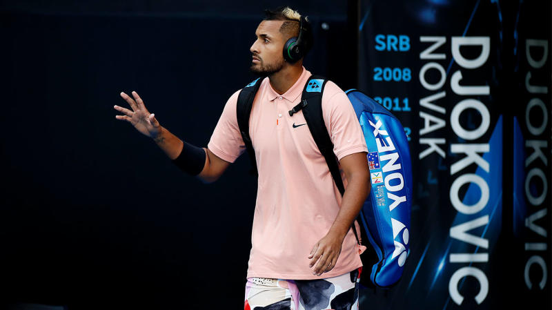 Nick Kyrgios waves as he walks on court at the Australian Open.