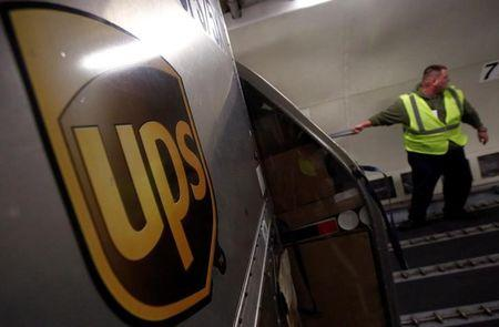 FILE PHOTO: A United Parcel Service (UPS) employee unloads packages from the cargo of an airplane at the Regional Air Hub in Rockford