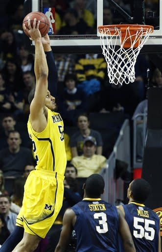 Michigan forward Jordan Morgan (52) leaps for a dunk in the first half of an NCAA college basketball game against West Virginia at the Barclays Center, Saturday, Dec. 15, 2012, in New York. (AP Photo/John Minchillo)