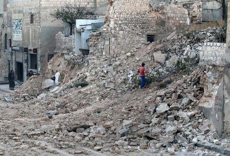 A civilian collects tree branches amid the rubble of a damaged site in the rebel-held besieged Qadi Askar neighbourhood of Aleppo. REUTERS/Abdalrhman Ismail