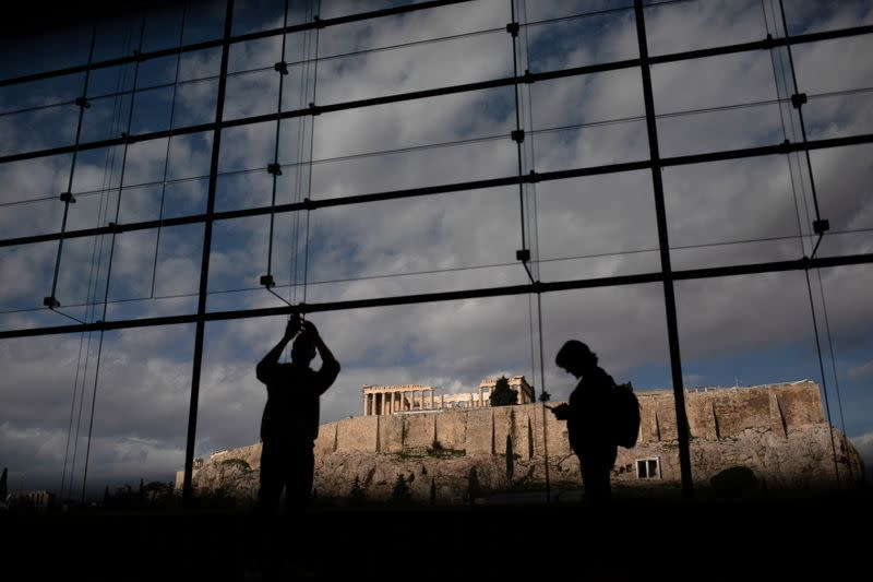 FILE PHOTO: Visitors take pictures of the Parthenon temple seen in the background, as they visit the Parthenon Gallery of the Acropolis Museum, in Athens