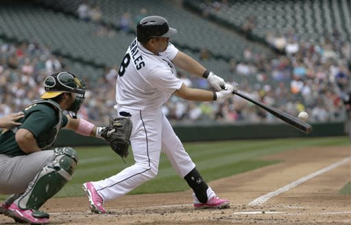 Seattle Mariners' Kendrys Morales connects for a three-run home run against the Oakland Athletics in the first inning of the American League MLB baseball game Sunday, May 12, 2013, in Seattle. (AP Photo/Elaine Thompson)
