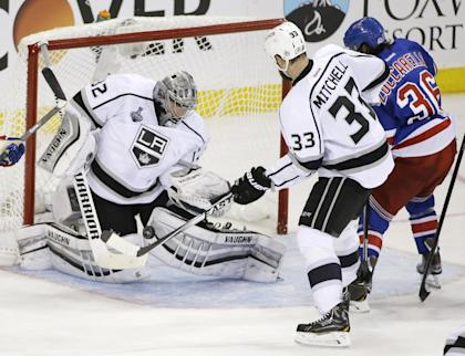 Kings goalie Jonathan Quick blocks a shot by Rangers winger Mats Zuccarello as Willie Mitchell helps defend during Game 3 of the Stanley Cup final Monday in New York. (AP)