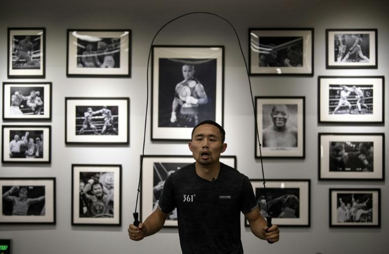 Zhang Fangyong trains at a Beijing boxing gym in front of a wall adorned with famous boxers including Floyd Mayweather and Manny Pacquiao