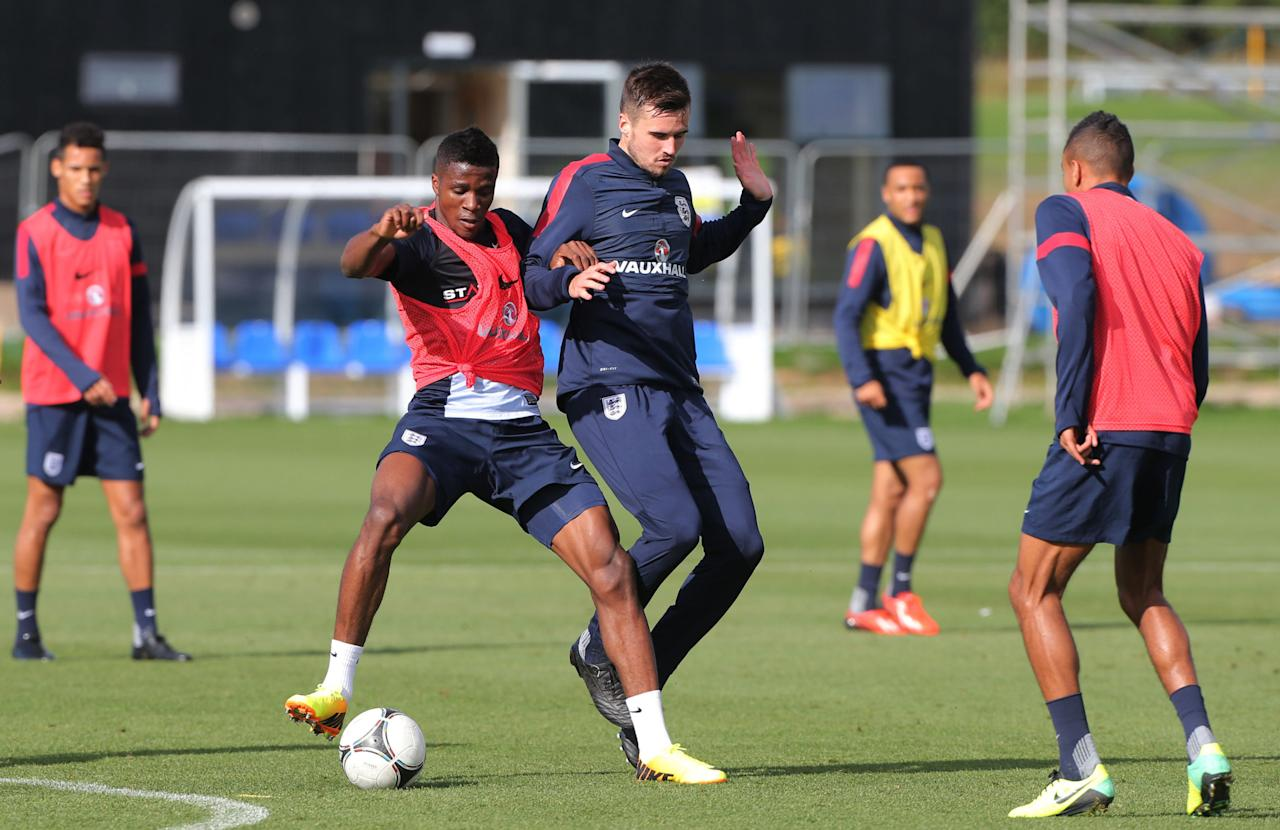 England's U21 players Wilfried Zaha tussles with Carl Jenkinson during a training session at St George's Park, Burton.
