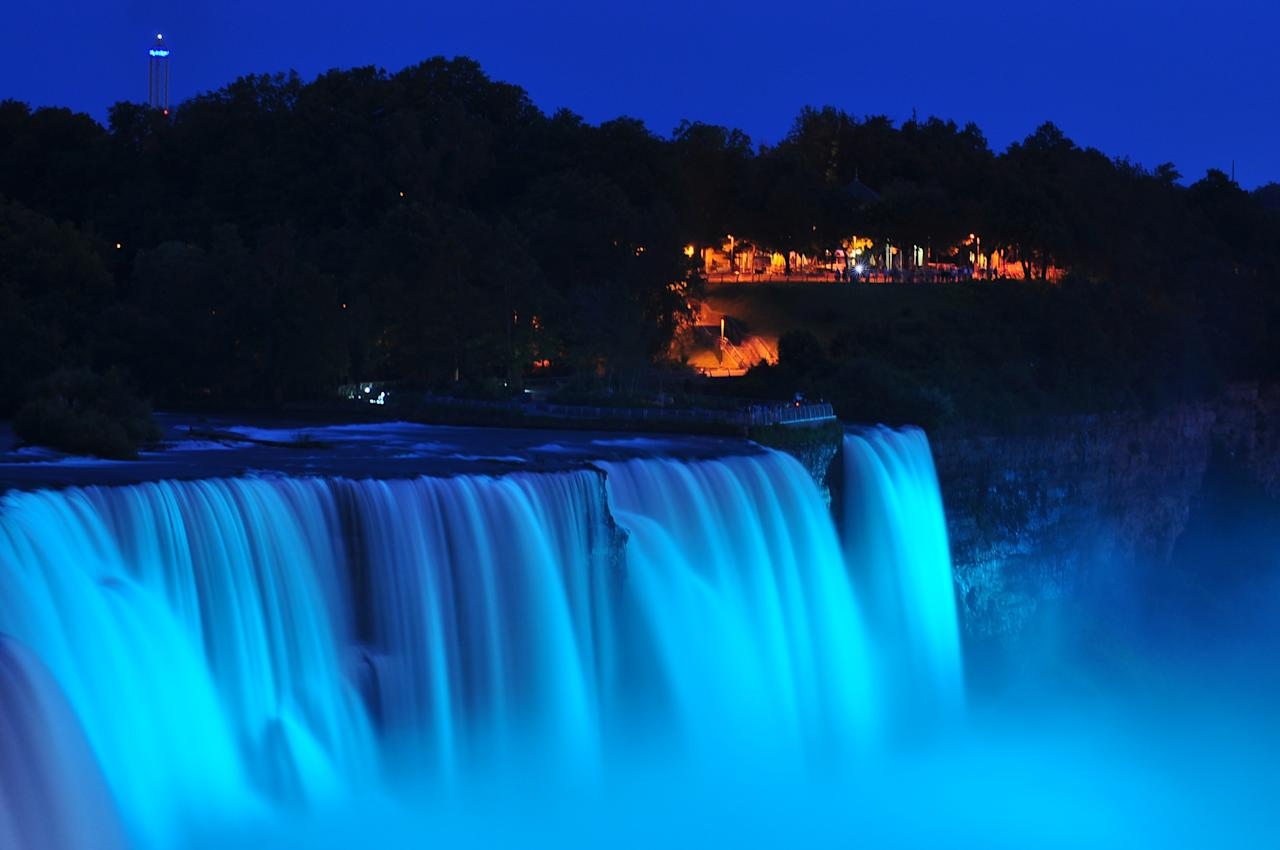 NIAGARA FALLS, NY - JULY 22: Visitors to Niagara Falls receive notice of the sex of the royal baby indicated by the blue light illuminating the falls in Niagara Falls, New York. The Royal couple,The Duke and Duchess of Cambridge, had a baby boy who was born at 16.24 BST and weighed 8 pounds, 6 ounces. The child, who is now third in line to the throne, has yet to be named. (Photo by John Normile/Getty Images)