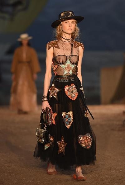 <p>A model in an embroidered dress and bolero hat walks the runway during the first cruise collection by Maria Grazia Chiuri for Dior show in Calabasas, Calif. (Photo: Getty Images) </p>