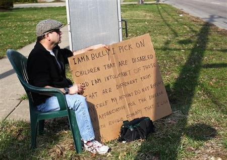 "Aviv sits with an ""I am a bully"" sign at a street corner in the Cleveland suburb of South Euclid"