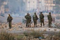 Israeli soldiers watch with Palestinian students from Birzeit University in the West Bank protest against the ongoing Israeli offensive on the Gaza Strip November 18, 2012