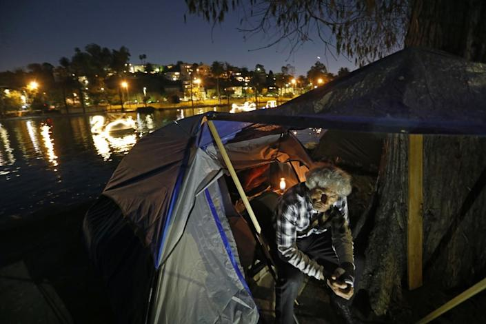 A man sits outside his tent next to a lake at night