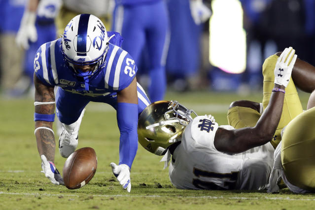 Duke safety Lummie Young IV (23) reaches to recover a fumble against Notre Dame safety Jalen Elliott (21) during the first half of an NCAA college football game in Durham, N.C., Saturday, Nov. 9, 2019. (AP Photo/Gerry Broome)
