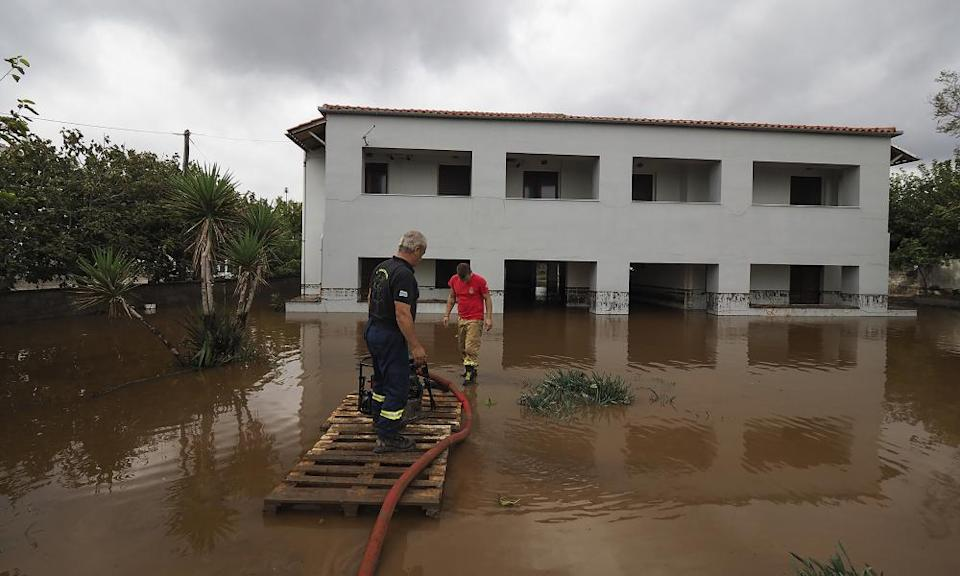 Firefighters pump water following a flood at the village of Agia Anna, at the northern part of Evia.