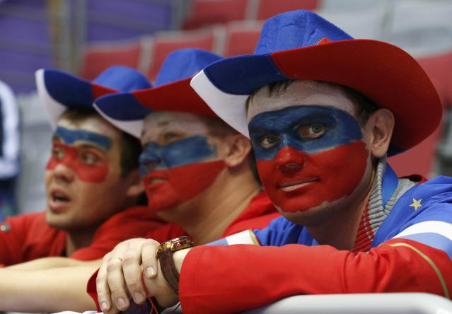 Fans with their faces painted in the colours of the Russian flag look on before the men's preliminary round ice hockey game between Russia and USA at the Sochi 2014 Winter Olympic Games February 15, 2014. REUTERS/Jim Young (RUSSIA - Tags: SPORT ICE HOCKEY OLYMPICS)