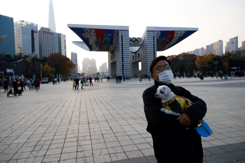 Man holding a pet dog takes a walk in Seoul