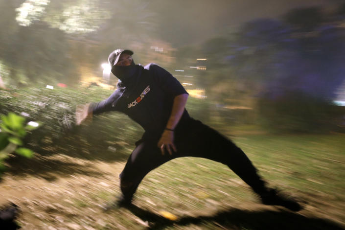 A protestor hurls a rock at police during clashes in Barcelona, Spain, Wednesday, Oct. 16, 2019. (Photo: Emilio Morenatti/AP)