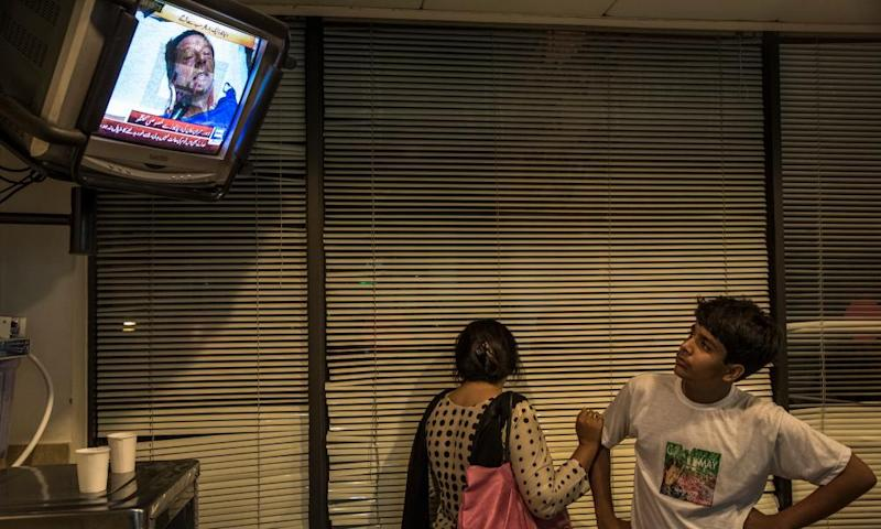People watch a 2013 television interview with Imran Khan in intensive care after he sustained an injury falling.