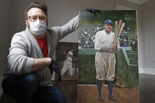 In this April 29, 2020, photo, baseball artist Graig Kreindler poses with his unfinished painting of Babe Ruth, right, as a painting of Josh Gibson rests behind him at his residence in the Brooklyn borough of New York. Over 200 of Kreindler's paintings of Negro Leagues players were on exhibit at the Negro Leagues Baseball Museum in Kansas City, Mo., when the coronavirus pandemic caused the museum to close. (AP Photo/Kathy Willens)