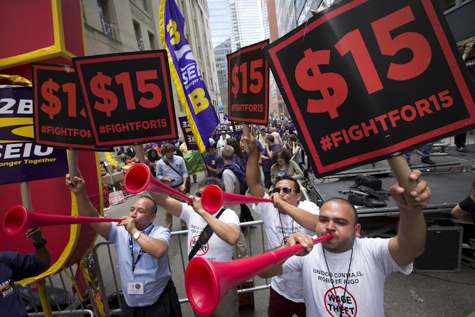 People in the streets blow horns and raise signs that say '$15 #FIGHTFOR15'
