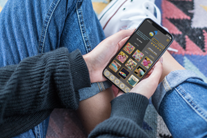 Mockup Of A Girl With Crossed Legs Holding An Iphone XS 25366