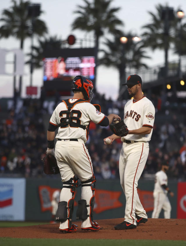 San Francisco Giants pitcher Tyler Beede, right, exchanges balls with catcher Buster Posey (28) in the first inning of a baseball game against the Arizona Diamondbacks Tuesday, April 10, 2018, in San Francisco. (AP Photo/Ben Margot)