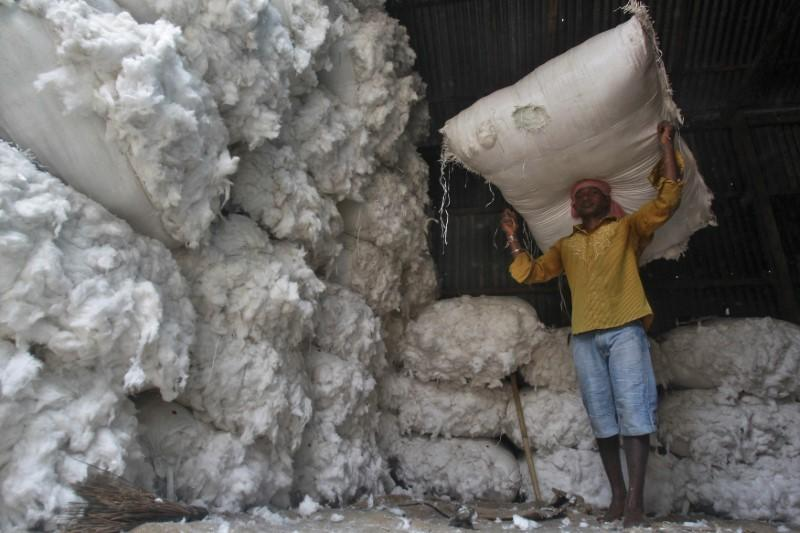 A worker carries a sack filled with cotton at a wholesale cotton market in Agartala