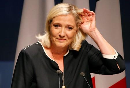 France's far-right leader Marine Le Pen waves before a speech for the next year's municipal elections in an end-summer annual address to partisans in Frejus