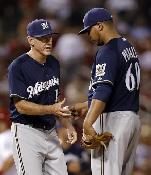 Milwaukee Brewers starting pitcher Wily Peralta, right, is removed from a baseball game against the St. Louis Cardinals by manager Ron Roenicke during the seventh inning Tuesday, Sept. 10, 2013, in St. Louis. (AP Photo/Jeff Roberson)