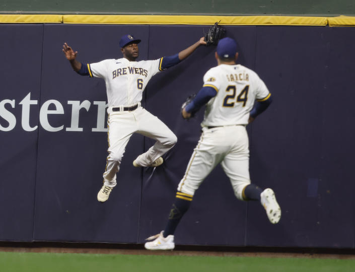 Milwaukee Brewers center fielder Lorenzo Cain leaps to catch a ball off the bat of St. Louis Cardinals' Tommy Edman during the second inning of a baseball game Wednesday, Sept. 22, 2021, in Milwaukee. Two Cardinal players tagged and scored on the play. (AP Photo/Jeffrey Phelps)