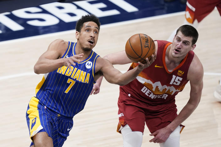 Indiana Pacers' Malcolm Brogdon (7) shoots against Denver Nuggets' Nikola Jokic (15) during the first half of an NBA basketball game, Thursday, March 4, 2021, in Indianapolis. (AP Photo/Darron Cummings)