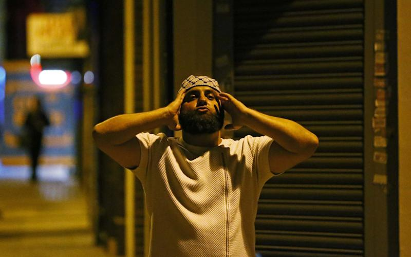 A man prays after a vehicle collided with pedestrians near a mosque in the Finsbury Park - Credit: Reuters