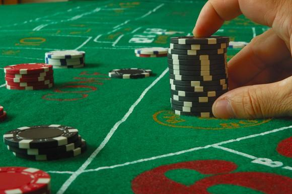 Hand next to large stack of chips on a craps table.