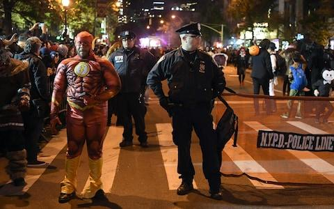 NYPD officers stand guard during the 44rd Annual Halloween Parade in New York - Credit: AFP