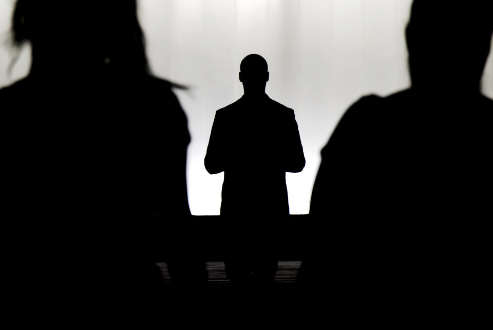 Silhouettes of a mystery man standing , watching and confronting two blurry persons in the dark