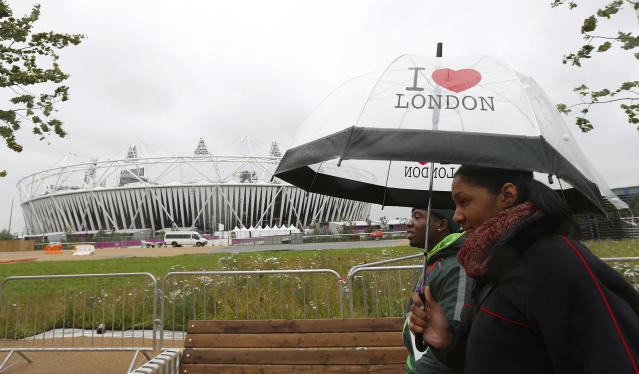 Pedestrians walk past the Olympic Stadium at the Olympic Park in Stratford, the location of the London 2012 Olympic Games, in east London July 16, 2012. REUTERS/Suzanne Plunkett (BRITAIN - Tags: SPORT OLYMPICS ENVIRONMENT)