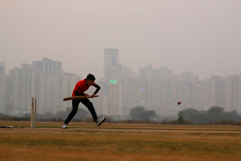A boy plays cricket amidst smog at a playground in Noida on the outskirts of New Delhi
