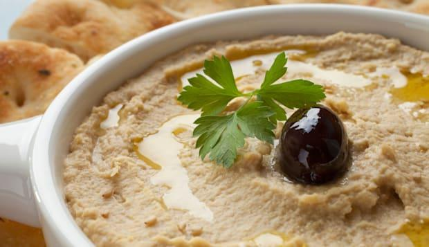 Hummus topped with olive oil, sesame seeds, parsley and an olive, served with Lebanese bread.