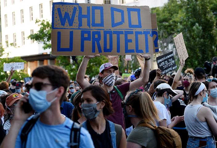 """<i>Demonstrators protesting the death of George Floyd hold up placards near Lafayette Park across from the White House on June 2 in Washington, D.C. The sign in the center reads: """"Who do u protect?"""" </i>"""