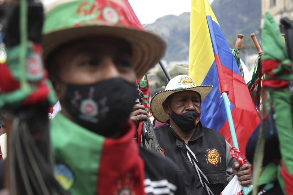 Members of the Indigenous Guard march against the government's handling of a wide range of issues including the economic fallout of the pandemic and implementation of the peace accord, in Bogota, Colombia, Wednesday, Oct. 21, 2020. Indigenous leaders, students and union members gathered in Plaza Bolivar waving flags and banners decrying the government nearly one year after massive protests rocked the country only to fizzle with little to show by way of reform. (AP Photo/Fernando Vergara)