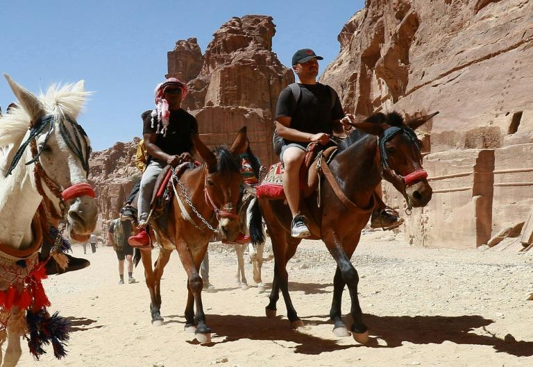 Tourists ride donkeys and horses as they visit Jordan's ancient city of Petra after it reopened following restrictions to stem the coronavirus pandemic