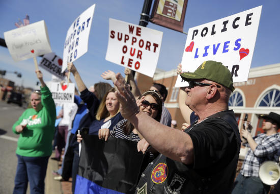 Pro-police demonstrators wave to passing cars Sunday in front of the Ferguson Police Department. (Jeff Roberson/AP)