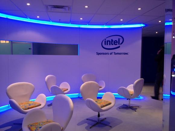 Room with six chairs, curved wall with blue lights on baseboard and ceiling trim, and Intel logo on wall.