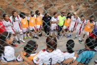 Deportivo Petare Futbol Club's players talk before a match in Caracas