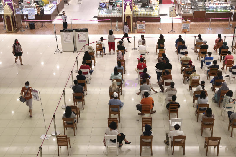 People sit spaced apart as a precaution against the new coronavirus outbreak while waiting for their turn to be allowed into a supermarket to shop, at AEON shopping mall in Tangerang, on the outskirts of Jakarta, Indonesia, Friday, May 22, 2020. Indonesia has seen a surge in coronavirus infections ahead of this this weekend's celebrations marking the end of Ramadan, raising questions about the commitment to the virus fight from both the government and the public. (AP Photo/Tatan Syuflana)