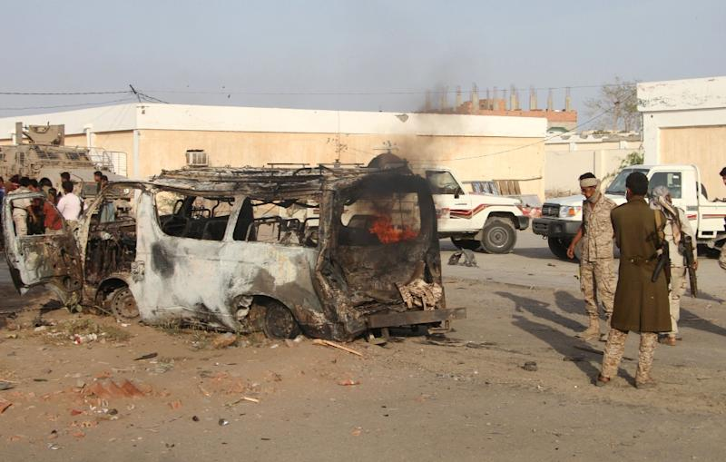 Yemenis check a burning vehicle following a suicide car bombing in Huta, the capital of the southern province of Lahj, a bastion of Al-Qaeda jihadists, on March 27, 2017