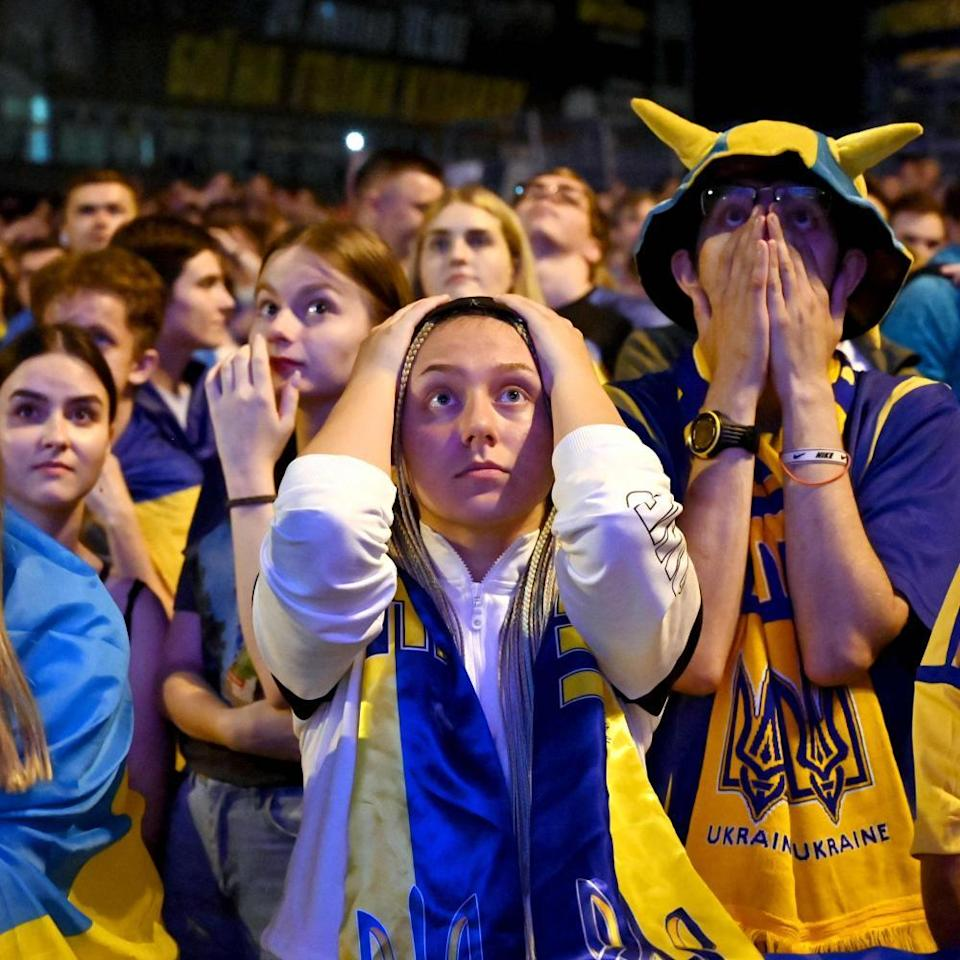 Ukraine's fans react as they watch on a giant screen the broadcast of the quarter-final football match aganst England.