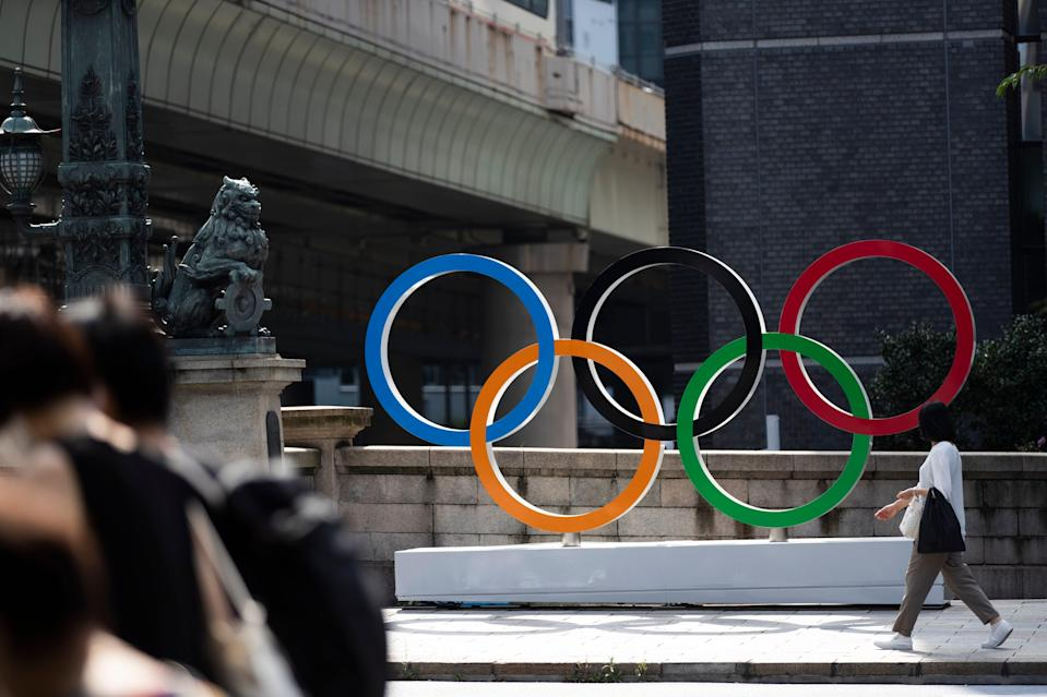 A woman walks by the Olympic rings installed by the Nippon Bashi bridge in Tokyo on Thursday, July 15.