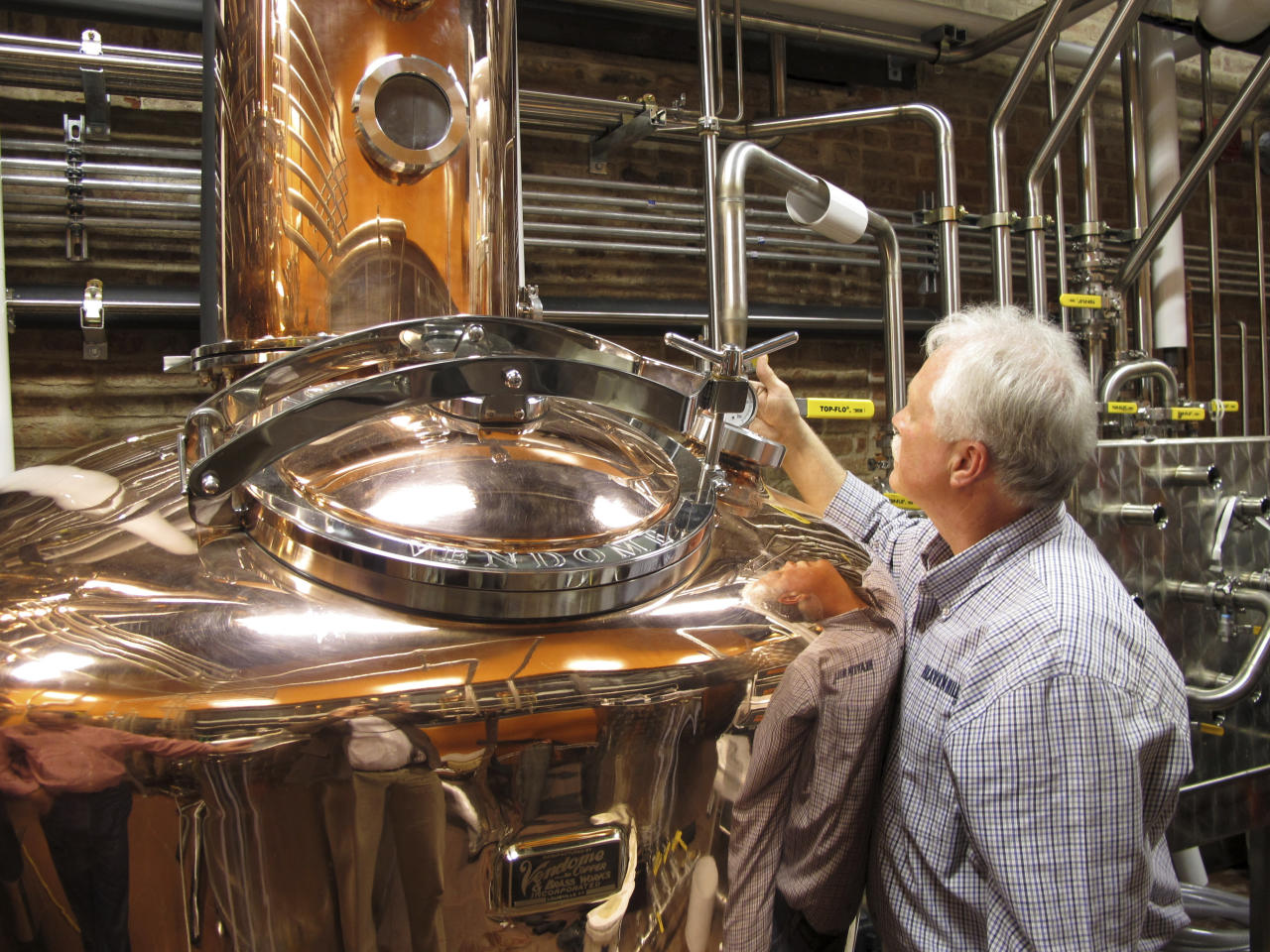 FILE - In this Wednesday Nov. 13, 2013, file photo, Charlie Downs, the artisanal craft distiller at a new Heaven Hill Distilleries tourism attraction in downtown Louisville, Ky., checks gauges on a still that will produce small batches of whiskey. In an effort to woo Amazon's second headquarters to their area, Louisville is playing up its role as the gateway to Kentucky bourbon country. (AP Photo/Bruce Schreiner, File)